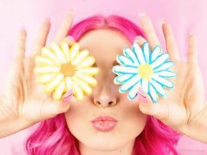 Fille aux cheveux roses avec des gateaux en forme de fleur devant les yeux