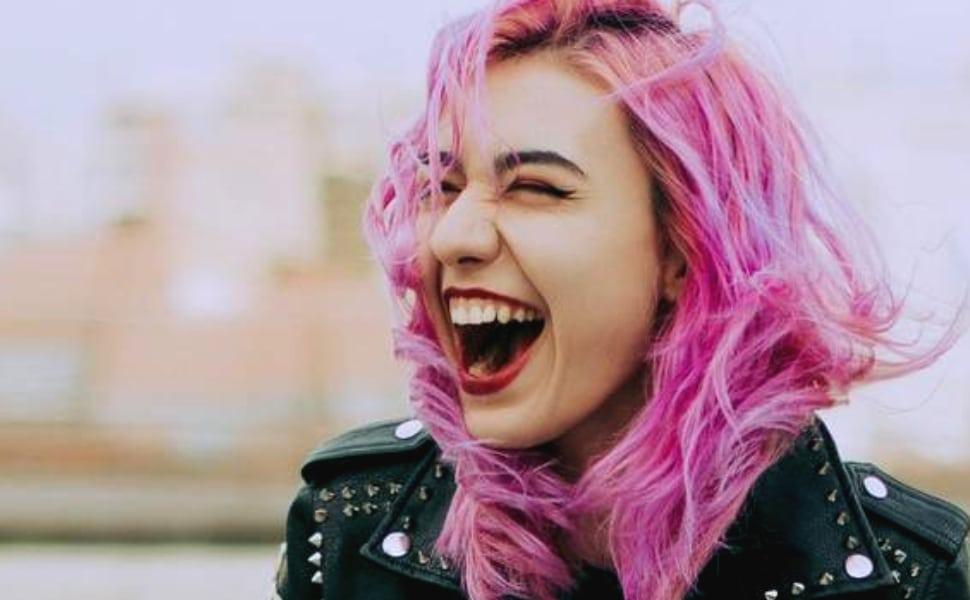 jeune femme aux cheveux roses riant aux éclats