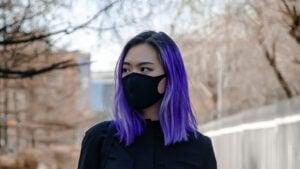 Jeune fille aux cheveux violets avec un masque en tissu