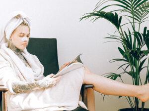 Jeune fille soignant ses cheveux et lisant un magazine