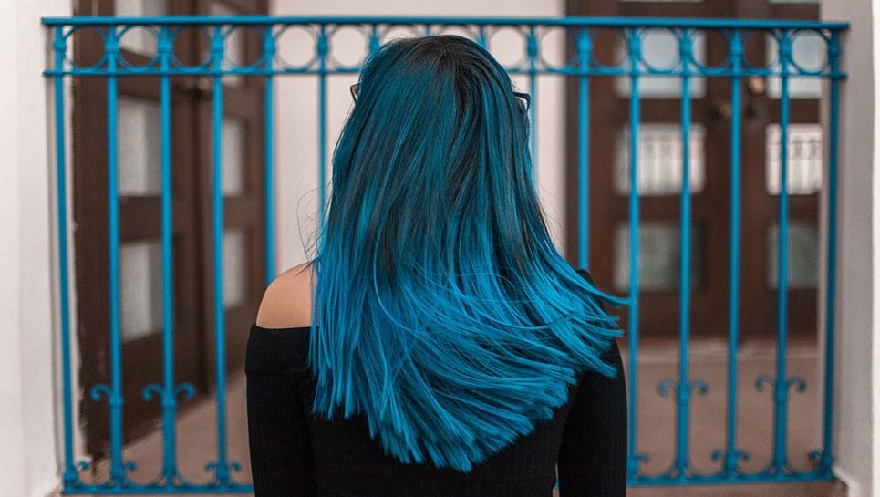 Cheveux longs bleus devant une grille bleu