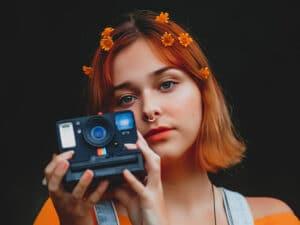Jeune fille aux cheveux orange avec un appareil photo polaroid