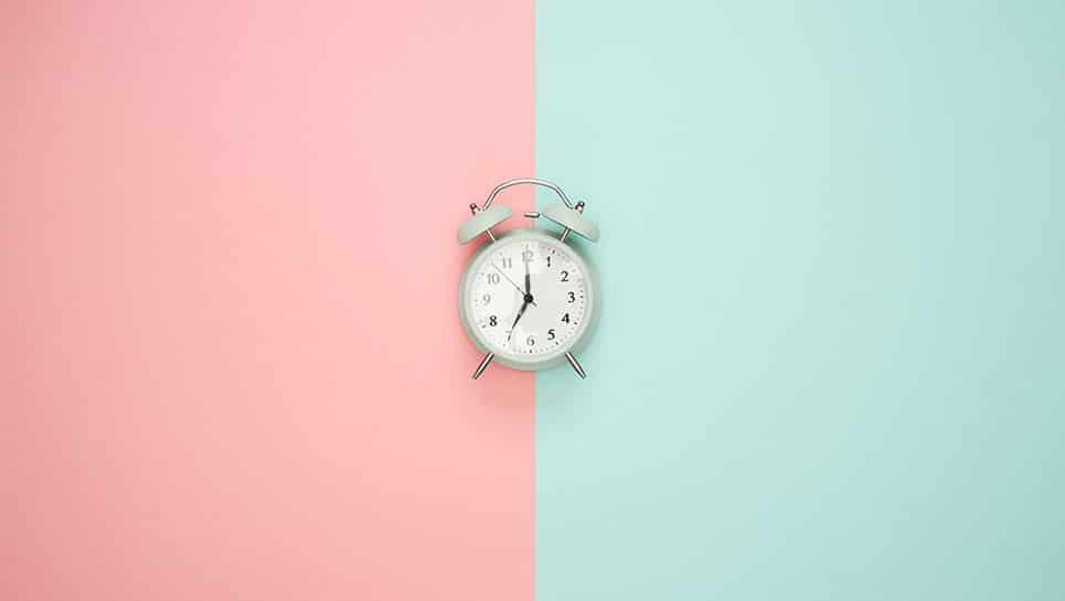 Horloge sur fond pastel indiquant le temps de la tenue d'une coloration