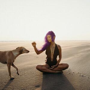 Une fille aux cheveux violet avec son chien à la plage