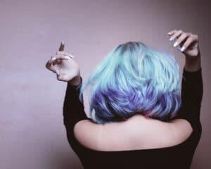 Femme aux cheveux mi-longs colorés en couleurs pastelles et gris, de dos, avec les bras en l'ai pour montrer sa coloration cheveux