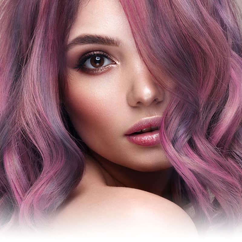 Portrait rapproché de femme aux cheveux colorés avec les colorations permanentes Yummy Colours, dans les tons de violet, lavande et gris foncé
