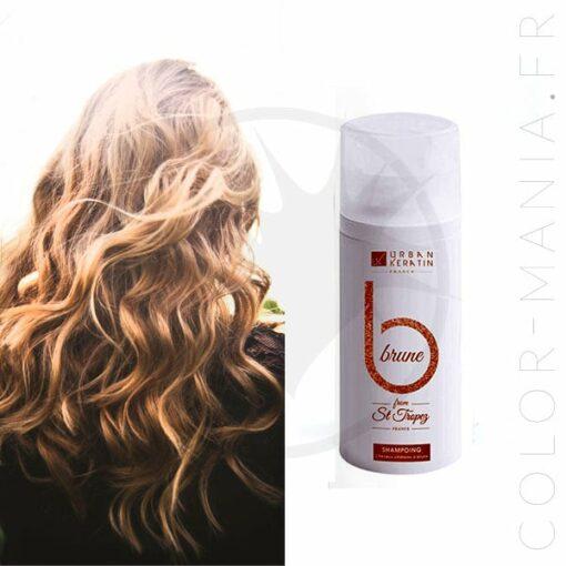 photo d'illustration avec une jeune femme aux cheveux bruns et une mini bouteille de 50 mL de shampoing pour cheveux bruns de la marque Urban Keratin