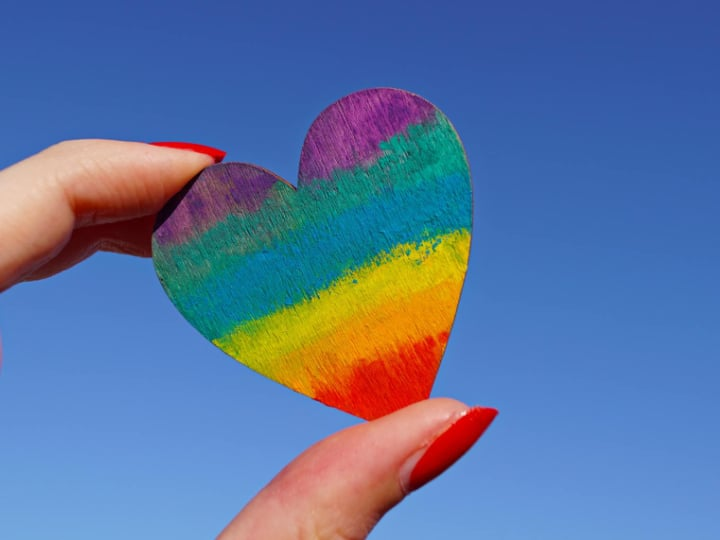 Petit coeur couleur arc-en-ciel tenu dans la main d'une femme