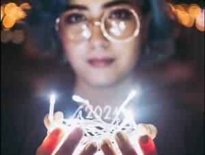 """Photographie d'une femme aux cheveux bleus tenant une guirlande de lumières dans ses mains, surmontée des chiffres """"2021"""""""