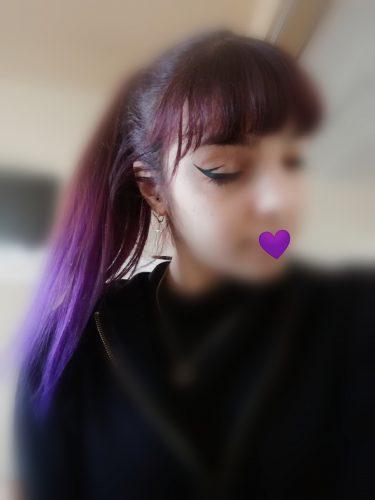 Jeune femme coiffée d'une queue de cheval aux cheveux violets