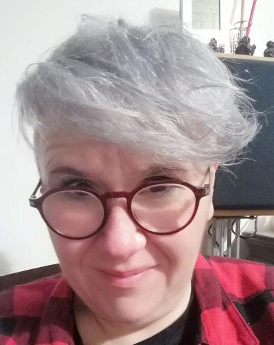 Femme aux cheveux blanc-gris avec lunettes de vue rouges