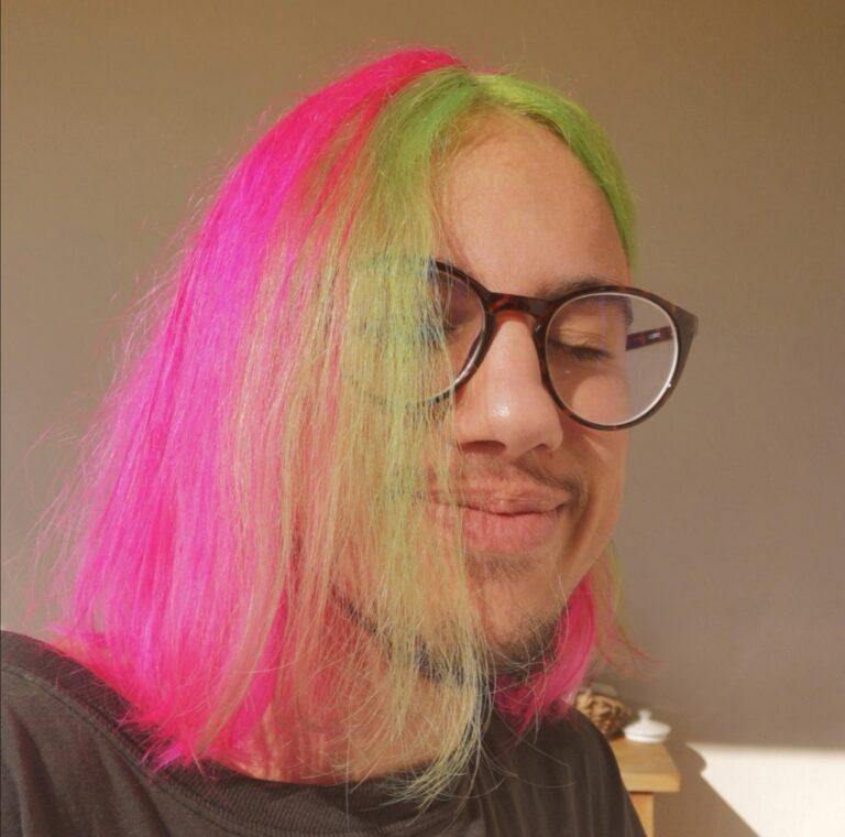 Jeune homme aux cheveux colorés en rose et vert
